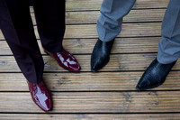 Close up of Groom and guests shoes while standing on decking at Whitsand Bay Fort, Cornwall