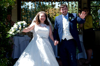 Bride and groom smiling and waving at guests at Lavender House hotel, Ashburton, Devon